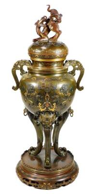 A fine Japanese two-colour patinated bronze koro, with gilt piquet work embellishments, silvered inlays and aplliques of coral and mother-of-pearl, the pierced and domed cover having Kylin surmount, dragon banded insert, the two-handle bulbous body with s