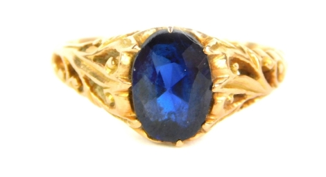 A sapphire set dress ring, with foliate carved shoulders and yellow metal shank, 2.7g all in.