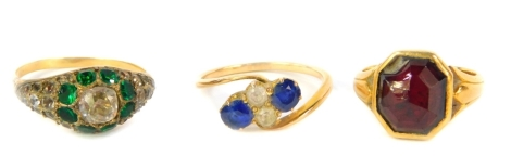 Three gem set dress rings, including sapphire and white stone example, all set in yellow metal.