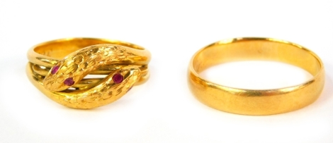 A Victorian gold wedding band with inscription, unhallmarked, 4.5g and an interlinked serpent ring, set with ruby eyes and in a yellow metal shank engraved 22C (2).