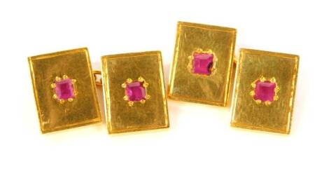A pair of cufflinks, set with rubies and cast in yellow metal.