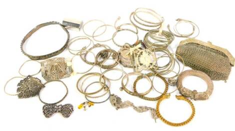 A quantity of mainly Indian and Eastern white metal, including bangles, slave and torc bracelets, chain mail evening purse, etc.