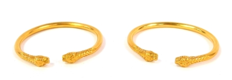 A pair of bracelets, cast with lion mask terminals, unhallmarked yellow metal.