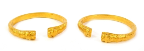 A pair of open bracelets, cast with stylised ends, unhallmarked yellow metal.