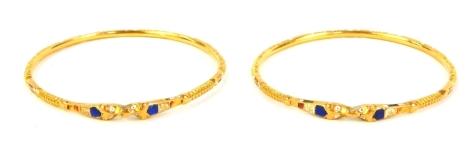 A pair of circular bangles, with enamel decoration, unhallmarked yellow metal.