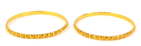 A pair of circular bangles, with faceted decoration, unhallmarked yellow metal.