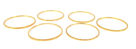 A set of six circular bangles, with chased decoration, unhallmarked yellow metal.