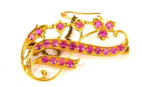 A floral scrolling brooch, with rubies set in a yellow metal mount, 4.5cm wide.