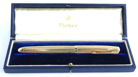 A Parker 51 9ct gold fountain pen, with engine turned decoration, stamped 9, 0.375, in blue leather case, 14cm long.