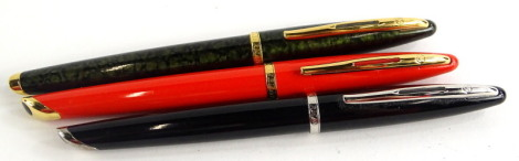 Three Waterman fountain pens, one with green and gold marbled effect, one black, one orange respectively, two with gold plated mounts.