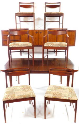 A McIntosh and Co Limited 1960's Rosewood dining suite, comprising a sideboard, with a pair of doors opening to reveal a shaped shelf, flanked to the left by three drawers, the top drawer fitted, to the right by a drop down flap revealing a drinks cabinet