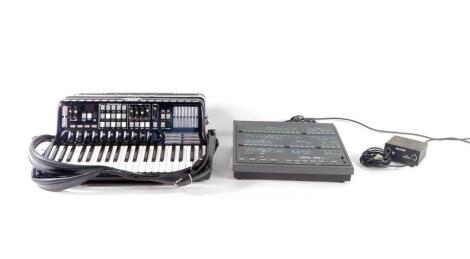 An Elka Cassotto midi piano accordion, with forty one keys, one hundred and twenty bass buttons and seven registers, cased, together with a midi power box and an Elka OMB3 synthesizer.