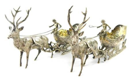 A pair of Continental silver bonbon dishes, modelled as reindeer pulling sleighs, surmounted with putti, JR and Company Limited, London 1962, 26.85oz. (AF)