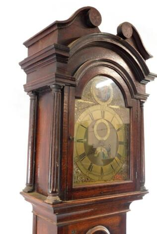 A Georgian oak cased longcase clock by Gamwel of Alford, the brass break arch dial with rococo scroll spandrels, chapter ring bearing Roman and Arabic numerals, subsidiary seconds and date dials, beneath a Tempus fugit circular aperture, painted with a wi