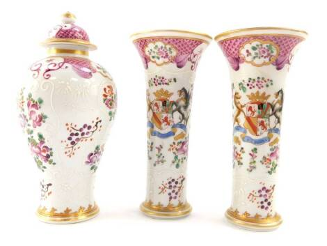 A Samson late 19thC porcelain garniture of vases, decorated in the Chinese export style with armorials and flowers against a scale famille rose ground, comprising a baluster shaped vase and cover, 17.5cm high, and a pair of trumpet shape vases, 15.5cm hig