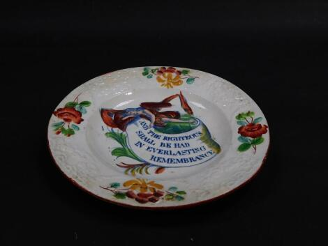 """An early 19thC pearl ware commemorative tea plate, clobbered and transfer decorated in blue and white, with an angel and scroll """"and the righteous shall be had in ever lasting remembrance"""" within a moulded border of floral swags, roses and other flowers,"""