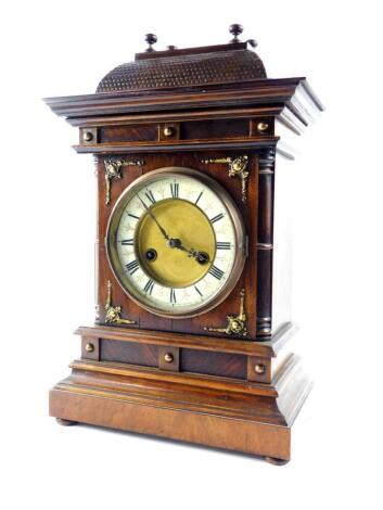 A German late 19thC oak and mahogany cased mantel clock, by the Hamburg American Clock Company, circular brass dial with enamelled chapter ring bearing Roman numerals, eight day movement with coil strike, the case of architectural form, no. 1068, with key