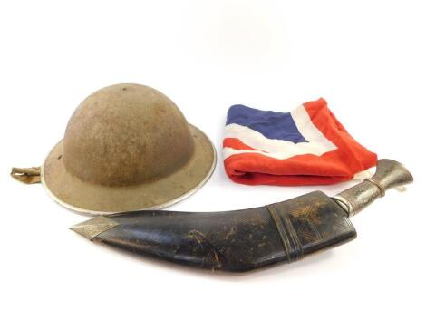 A World War I Brodie helmet, with leather lining and white metal trim, a kukri with damascene decoration, in a leather scabbard, and a Union Jack flag. (3)