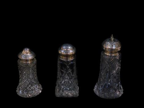 Three Edward VII and George V cut glass sugar casters, with silver lids, Birmingham 1903, 1911 and 1912.