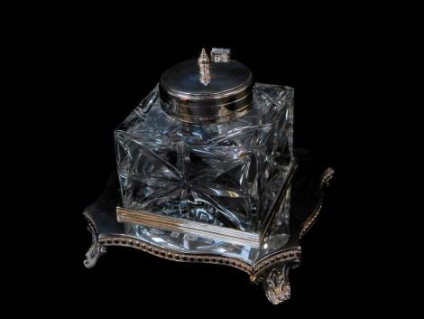 A silver and cut glass inkwell, the inkwell with plated mount and hinged lid, on a serpentine base with beaded rim, raised on leaf scroll feet, Mappin and Webb, London 1989, base 4.19oz.