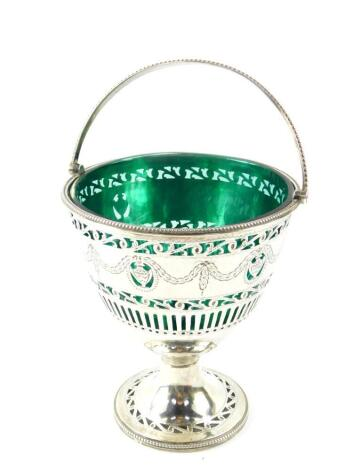 A George III silver sugar basket, with green glass liner, swing handle, pierced and engraved with classical urns, swags and foliate scrolls, oval shield reserve, crest engraved, William Bateman I, London 1820, 5.19oz.