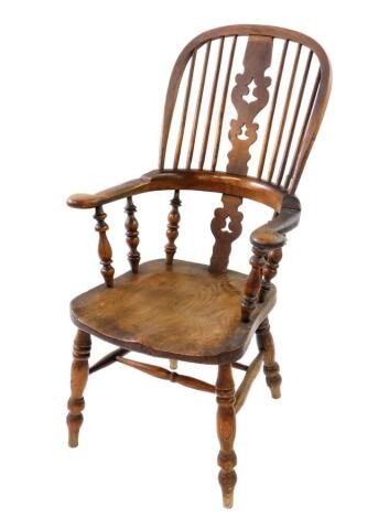 A Victorian oak and elm Windsor chair, with a carved splat and spindle back, solid saddle seat, raised on turned legs united by a double H framed stretcher.
