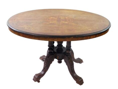 A Victorian walnut and inlaid tilt top loo table, the oval quarter veneered top inlaid with vases of scrolling leaves and line inlay, raised on five turned columns over four leaf carved cabriole legs, on castors, 90cm high, 111cm wide, 86.5cm deep.