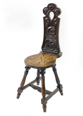 A Victorian oak spinning chair, with a scrolling leaf carved back and seat, raised on baluster turned legs untied by an H framed stretcher.