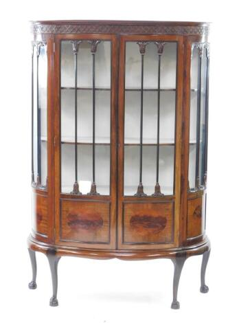 An early 20thC Chippendale style mahogany bowfront display cabinet, the pediment carved with blind fretwork above a pair of glazed and panelled doors flanked by side panels, opening to reveal three shelves, raised on cabriole legs and ball and claw feet,