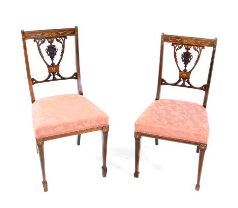 A pair of Victorian rosewood and inlaid salon chairs, with satin wood and ivory inlaid, with carved vase shaped splats, overstuffed seats, raised on tapering square legs, and spade feet.