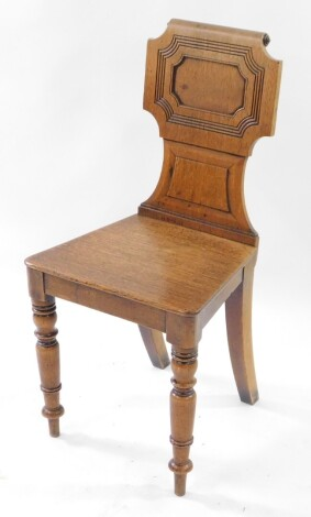 A Victorian oak hall chair, with a carved and scroll back and solid seat, raised on turned legs.