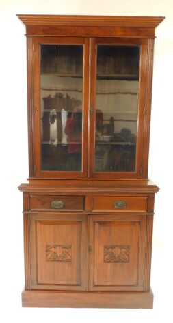 A Victorian mahogany cupboard bookcase, the outswept pediment over a pair of glazed doors opening to reveal three shelves, over two drawers above carved panelled doors, raised on a plinth base, 222cm high, 107cm wide, 43.5cm deep.