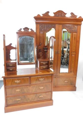 A Victorian walnut double wardrobe and dressing chest, by Blair and Kemp, Horncastle, the wardrobe with outswept pediment over a pair of carved and mirror set doors, the doors opening to reveal hanging hooks over a pair of deep drawers raised on a plinth