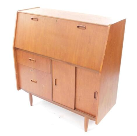 A Burolite teak bureau desk, the fall flap opening to reveal drawers and recesses, over two graduated drawers flanked by a pair of cupboard doors opening to reveal a shelf, raised on turned legs, 103.5cm high, 99cm wide, 41cm deep.