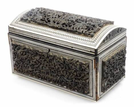 A 19thC heavily carved Anglo Indian padouk and sadeli double tea caddy, with domed top, with fitted interior, the exterior profusely decorated and raised with building surrounded by flowers and further panels, with an outer geometric border, 16cm high, 2