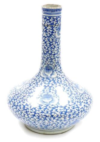 A Chinese porcelain blue and white bottle vase, with slender neck decorated with an all over design of scrolling peonies, unmarked, partial collectors label to base, probably 19th century. 31cm high.