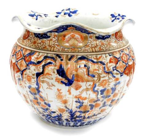 A large Japanese Imari Meiji period jardiniere, the flared rim above a ribbed circular body, profusely decorated with birds, buildings and flowers, predominantly in orange and blue, with an upper geometric floral border on circular foot, unmarked, 39cm hi