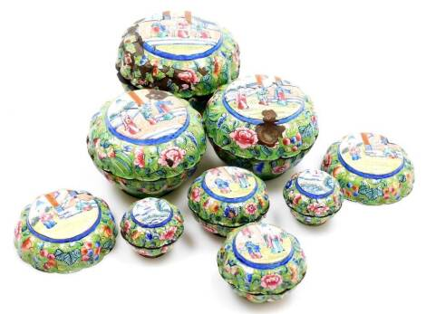 A graduated set of early 20thC Chinese Canton enamel jars and covers, each decorated with panels of figures to the lids, the bodies decorated with flowers, predominantly in pink, turquoise and blue on green ground, 10cm wide, etc. (a quantity)