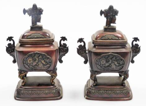 A pair of Japanese bronze incense burners, each with domed lids with Sambaso dancer knops, the shaped bodies flanked by scroll handles on scroll feet, terminating in domed bases, profusely decorated with panels of figures a Buddhist drum and trees, early