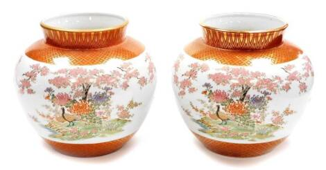A pair of Japanese Kutani porcelain jardinieres, decorated with pheasants chrysanthemums and cherry blossom between lappet and diaper borders in gilt, seal marks to the base. 20thC, 23cm high. (2)