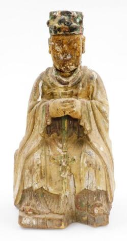 A Chinese painted wood figure, of a seated sage in flowing robes with polychrome hat, probably 18thC, 43cm high.