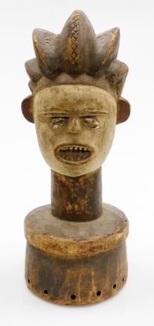 An African tribal hardwood head figure, with elongated features, shell eyes and open mouth, on a circular part pierced base, 45cm high.