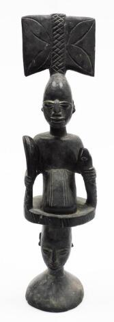 A heavily carved ebonised African tribal totem style figure, formed as two figures with elaborate features on a circular base, 54cm high.