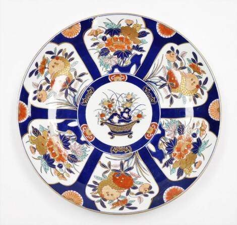 A Japanese Imari charger with basket of flowers, surrounded by panels of floral bouquets on a blue ground, gilt border, signed on the underside and with Made in Japan label, 20thC, 46cm diameter.