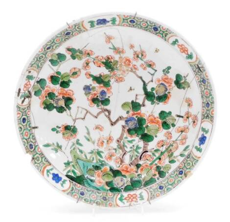 A Chinese Kangxi porcelain dish, profusely decorated with flowering shrubs, predominantly in orange, green and blue, with an outer floral banding broken by panels of flowers in blue and green, blue tripod censer mark to base, 28cm diameter. (AF)