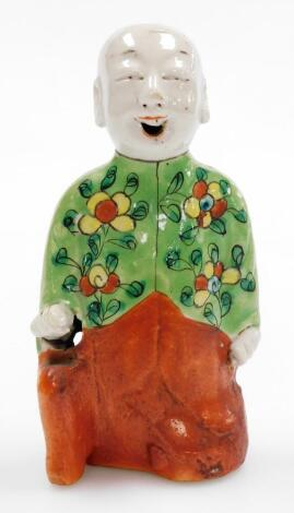 A Chinese spill holder modelled as a kneeling child with smiling expression, glazed predominantly in green, yellow and orange, 19thC, 17cm high.