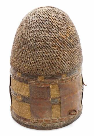 A 20thC African hide and woven measuring guard, with leather insert and entwined woven top, 28cm high. (hollow)