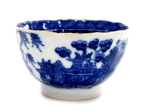 A Chinese export porcelain blue and white tea bowl, decorated with buildings, birds and trees with gilt shaped rim, 18th/19thC, 9cm wide.