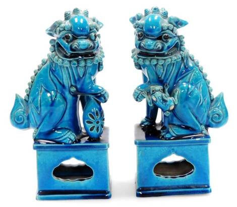 A pair of Chinese turquoise glazed pottery dogs of fo, each on shaped partially pierced bases, unmarked, 23cm high. (2)