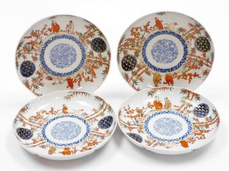 A set of four Japanese Imari porcelain plates, decorated with figures among bamboo and prunus, central underglaze blue floral medallion, four character Fuki Choshun mark (meaning Wealth, Nobility, Longevity and Youth), Meiji period. 23cm wide.